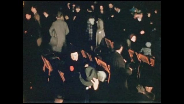"""1930s: Spectators stand and leave theater.  Actors perform on stage set.  Sign reads """"PETROLEUM FOR THE HOME AND FARM."""""""