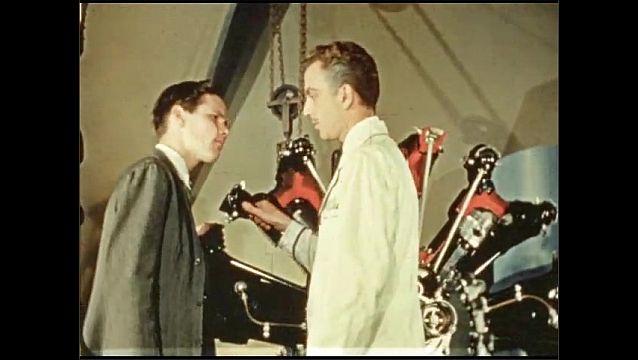 1930s: Actors speak on stage.  Machine.  Crowd watches animatronic oxen pull wagon.