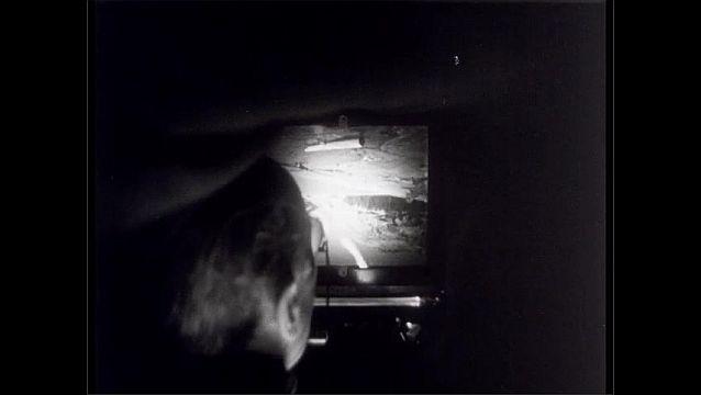 1950s: Man and woman adjust camera near mountain lake. Man looks at glass display of view camera. Hands adjust camera knob. Mountain picture comes into focus. View camera lens.