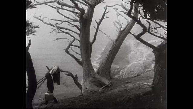 1950s: People leave rocky coast.  Man walks with camera.  Waves crash on shore.