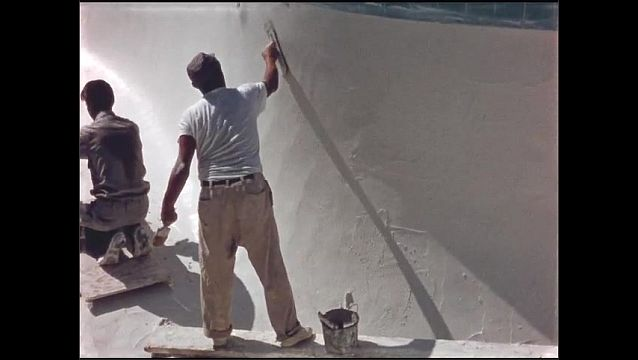 1960s: Men use trowel to spread plaster on wall of swimming pool.