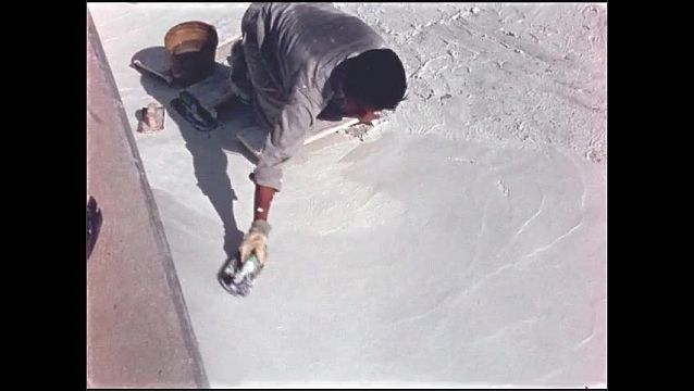 1960s: Man uses trowel to spread plaster in swimming pool.