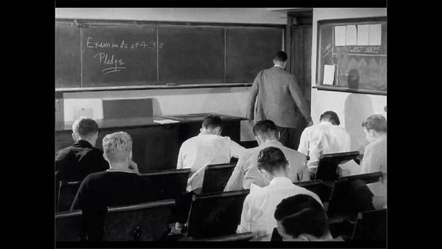 1950s: Teacher hands out papers to students. Teacher leaves room, students write on papers.