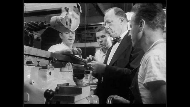 1950s: Teacher shows chemistry equipment to students. Teacher and students gather around equipment, talk. Teacher sits behind desk and talks to student.