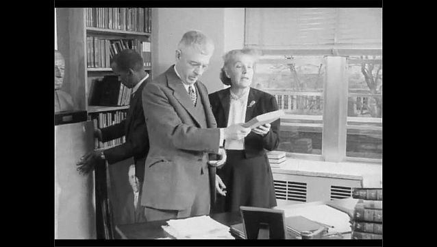 1950s: Bust of man. Man talks to woman, looks at papers.