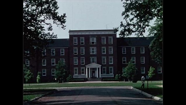 1950s: Students walk around campus. Large building.
