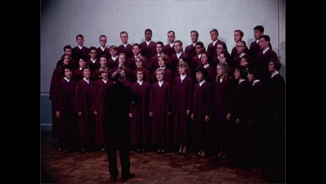 1950s: Man conducts choir.