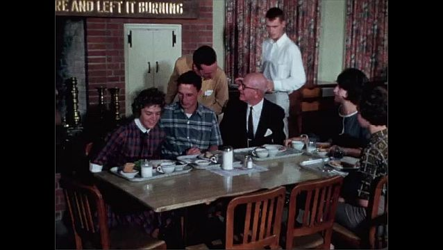 1950s: Women sit on couch, talk. Men and women sit down at table with food. Men sit on couch, talk.
