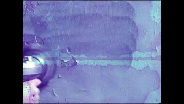 1960s: Man sands wall.