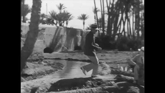 1940s: UNITED STATES: villagers watch men. Lady runs away. Men run.