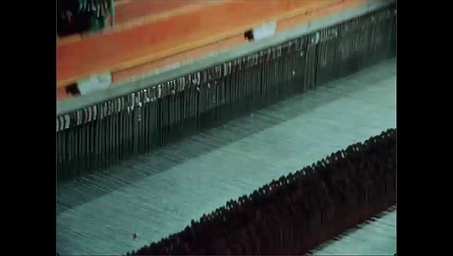 1950s: UNITED STATES: strands of cotton on machine. Fabric loom weaves cotton. Fabric on machine in factory. Cotton in testing laboratory.