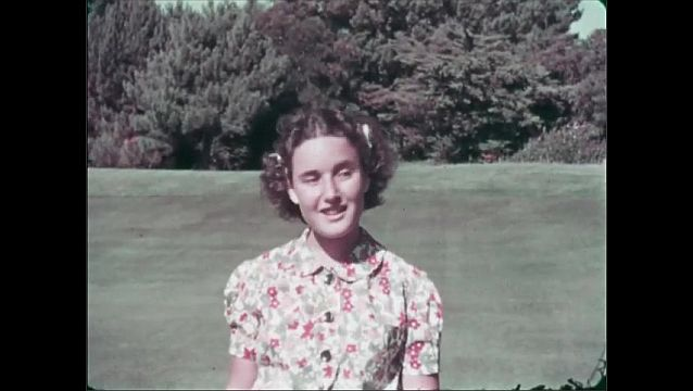 1940s: UNITED STATES: girl bounces ball on racket in garden. Boy plays with baby goats in garden.