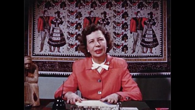 1940s: Woman sits and speaks at desk in art-filled office.