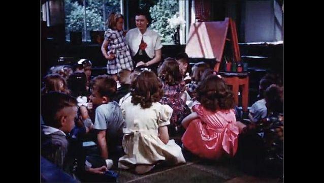1940s: Children walk into doors of elementary school. Teacher talks to students in classroom.