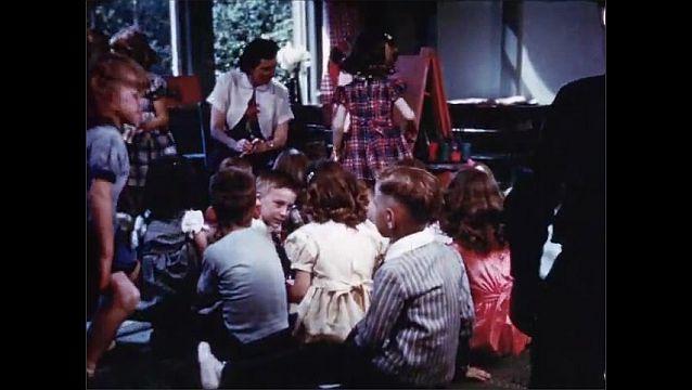 1940s: Teacher talks to students in classroom. Children sit in and walk around classroom.