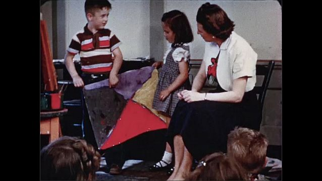 1940s: Children sit on floor in classroom. Students hold paintings and talk to students and teacher. Colorful tempura painting on paper. Students hold paintings and talk to class.