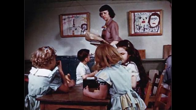 1940s: Girl and teacher sit at window in classroom and talk. Teacher carries stack of blank cards to table of students. Girl takes blank card from teacher.