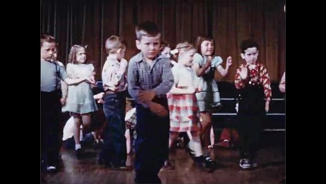 1940s: Teacher and students sit in auditorium and move hands to music. Students stand and wave hands. Students dance and march in circle.