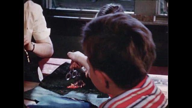 1940s: Hands sew yarn into burlap swatch. Girl sews yarn into burlap. Girls and boys pull needles and yarn through burlap.