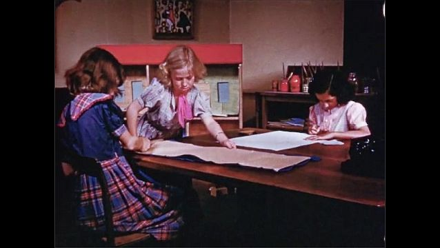 1940s: Girl writes on large paper with pen. Girls cut paper with scissors and write at table. Girls carry long piece of paper and lay it near dollhouse.
