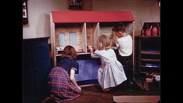 1940s: Girls lay felt on floor of dollhouse. Hands with crayon write lunch menu on paper. Girls and boy decorate large dollhouse. Boy hammers wooden blinds onto dollhouse. Girl places doll in house.