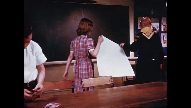 1940s: Boys color on large menu with crayons. Boys stand and students remove menu. Students carry paper menu from classroom to classroom.
