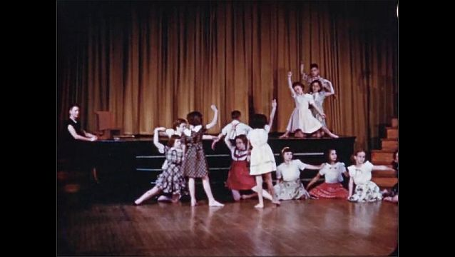 1940s: Boy emerges from curtains on stage and dances toward girl. Boys and girls dance barefoot in auditorium.