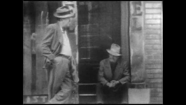 1940s: Cars drive past men talking on building stoop. Men walk and talk on city sidewalk.