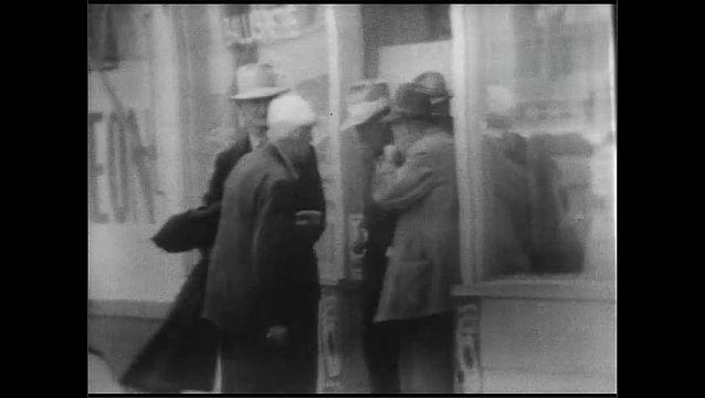 1940s: Men gather and talk in doorway of city café. Man runs across street in inner city.