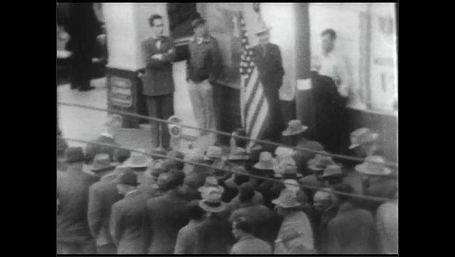 1940s: Men line up on street corner and wait to enter building.