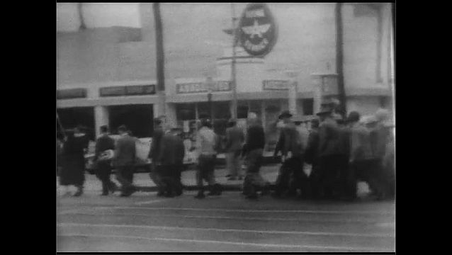 1940s: Salvation Army members carry flags and lead crowd of men across the street.