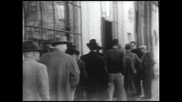 1940s: Men walk in line down sidewalk past pharmaceuticals building. Men walk in line and enter building. Man sings at podium.