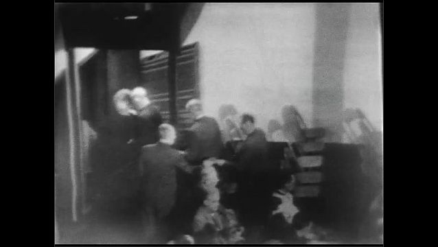 1940s: Man stands near door of church and accepts envelopes from men as they exit. Men hand donation envelopes to man in church aisle.