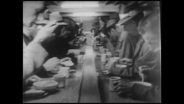 1940s: Men eat soup and sandwiches at long tables in cafeteria. Woman speaks to men as they exit cafeteria.