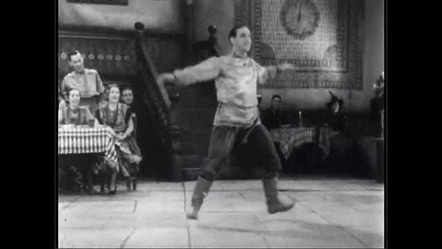 1930s: UNITED STATES: man dances traditional Russian dance as choir sing. Diners watch man dance.