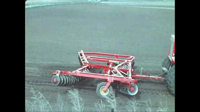 1970s: UNITED STATES: tractor in field. Tractor lowers plough