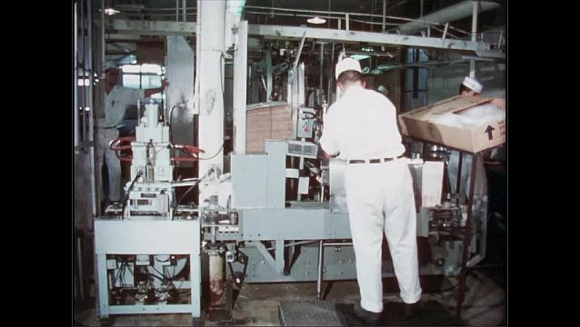 1950s: Man stands at machine in factory plant, packing boxes as they go by on conveyor belt through machine.