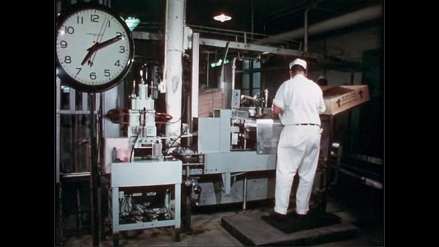 1950s: Man stands at machine in factory plant, packing boxes with filled bags of milk, as they go by on conveyor belt through machine.