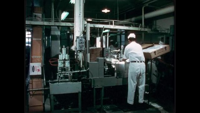 1950s: Unattended machine in factory plant. Man steps up to machine and places bags with nozzles to it. Bags fill with milk.