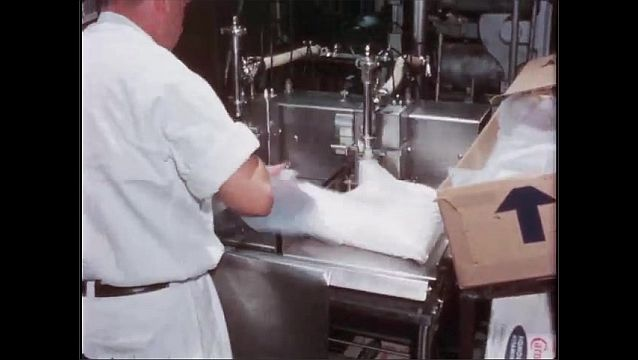 1950s: As man stands at factory machine, filling bags with milk, box is raised up. Filled bags go in boxes and down conveyor belt. Process repeats.