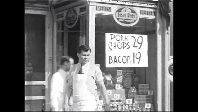 1940s: UNITED STATES: pork chops and bacon signs in window. Man stands outside grocers store.