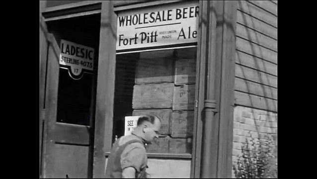 1940s: UNITED STATES: Man stands outside meat shop. Man with barrel. Men unload wagon.