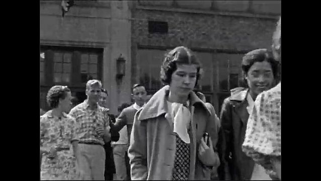 1940s: UNITED STATES: high school students leave school. Boy waves at camera. End of school day