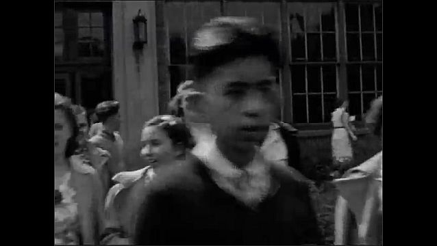 1940s: UNITED STATES: students leave high school. Girl smiles at camera. Teenagers at school. Girls walk arm in arm.