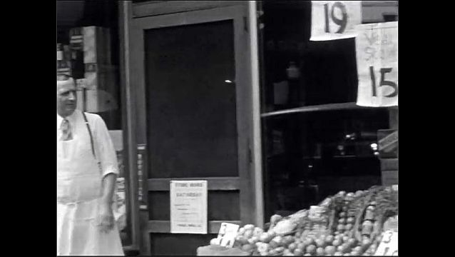 1940s: UNITED STATES: veal stew promotion in window. Men stand outside greengrocers store in street