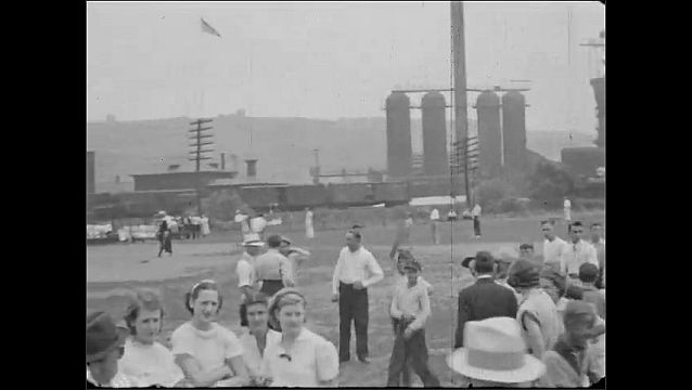 1940s: UNITED STATES: man and lady smile at camera. Children wave at camera. Lady with baby. Industrial works behind baseball pitch