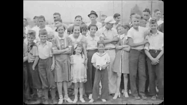 1940s: UNITED STATES: town on field pose for camera. Policeman in uniform. Boys in baseball kit.