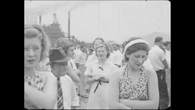 1940s: UNITED STATES: brass band play at community event in field. Ladies and girls look at camera.
