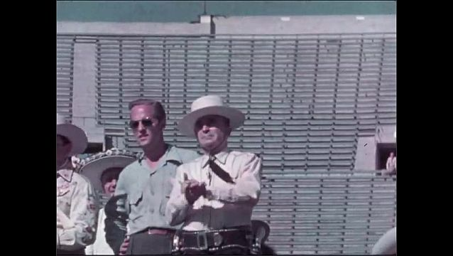 1940s: Man wearing sheriff uniform in stadium bleachers, claps. Men in police uniforms ride horses in formation on track before crowd for parade. Sheriff claps. Men in uniform ride horses in parade.