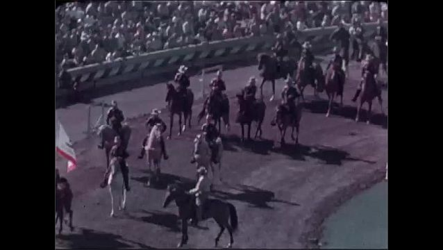 1940s: Audience in bleachers of stadium clap as man in fancy sheriff uniform stands, takes off hat and turns to them. Officers sit on horses around track in stadium.